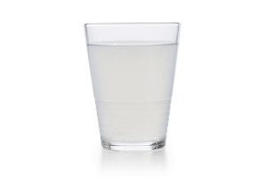 Full glass of tap water obscured by small particles. Concept for unhealthy water supply for people in developing countries.
