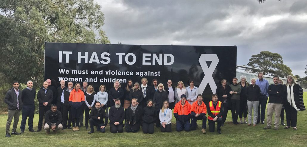 Image of Westernport Water staff standing in front of White Ribbon billboard sign